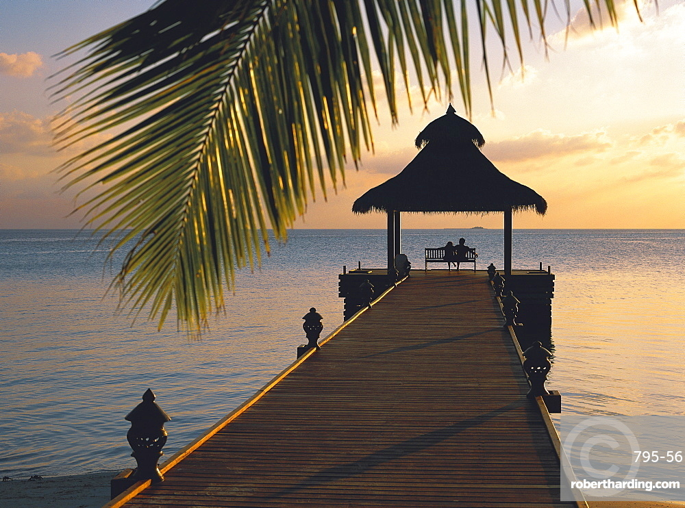 Couple looking at sunset on a jetty, Maldives, Indian Ocean, Asia