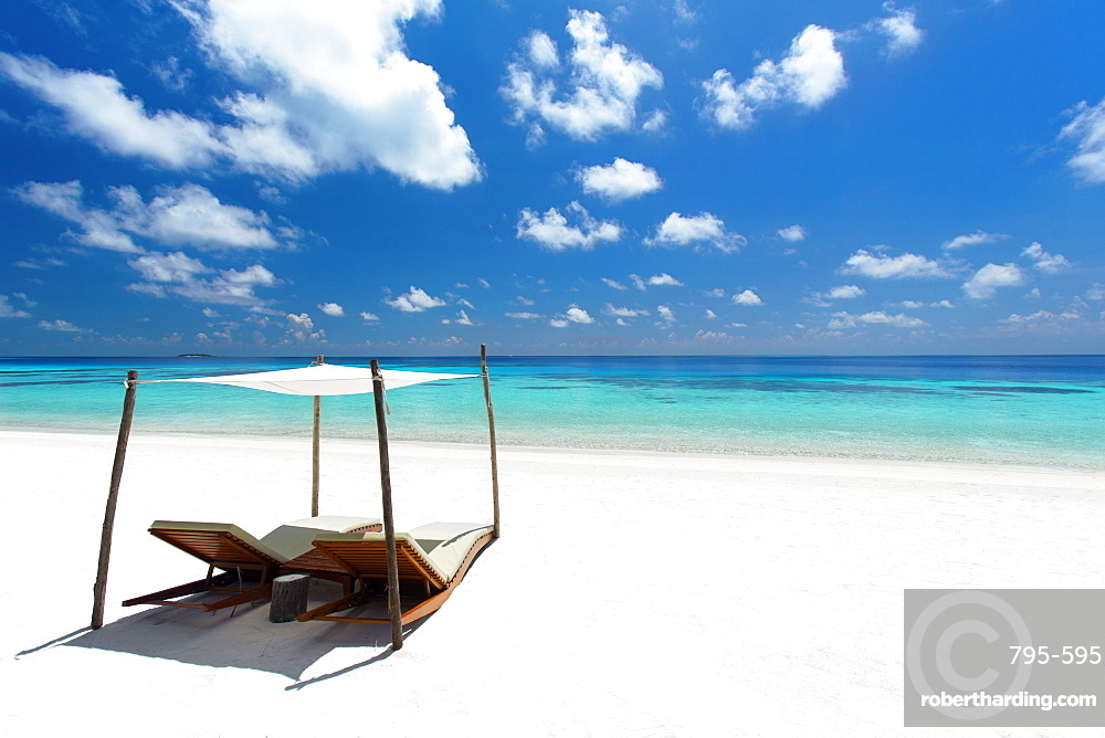 lounge chairs on tropical white sandy beach