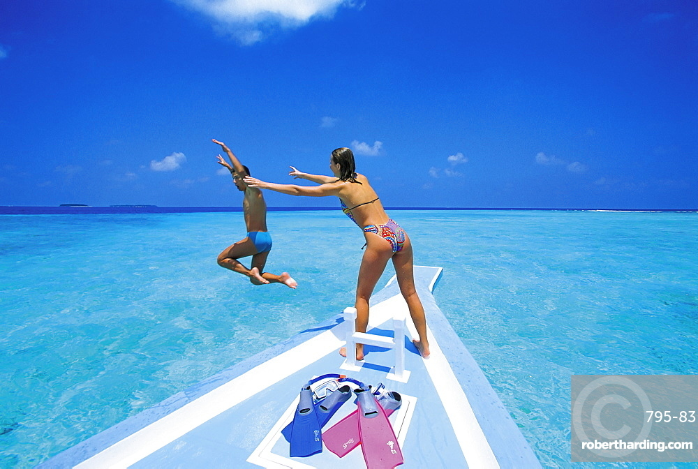 Couple at front of boat, man jumping in water, Maldives, Indian Ocean, Asia