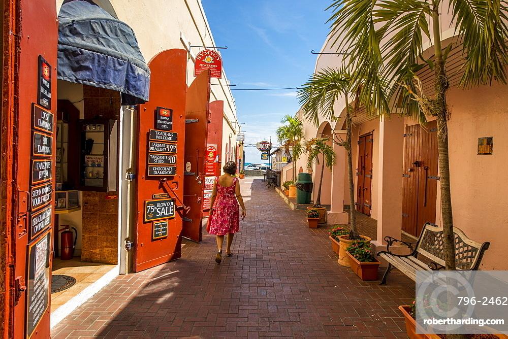 Woman walking by shop in downtown Charlotte Amalie, St. Thomas, US Virgin Islands, Caribbean