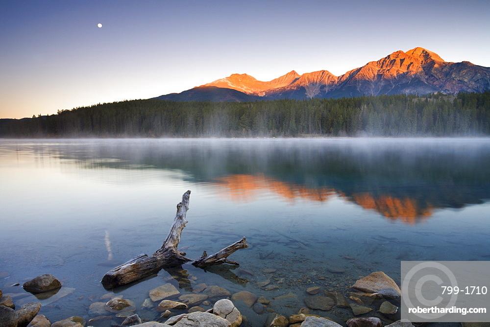 The first rays of sunshine illuminate Pyramid Mountain and reflect in Patricia Lake, Jasper National Park, UNESCO World Heritage Site, Alberta, Canada, North America