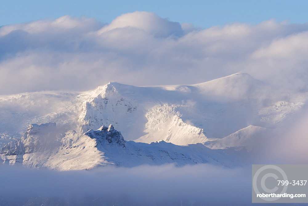 Snow covered mountains appearing through clouds, Iceland, Polar Regions