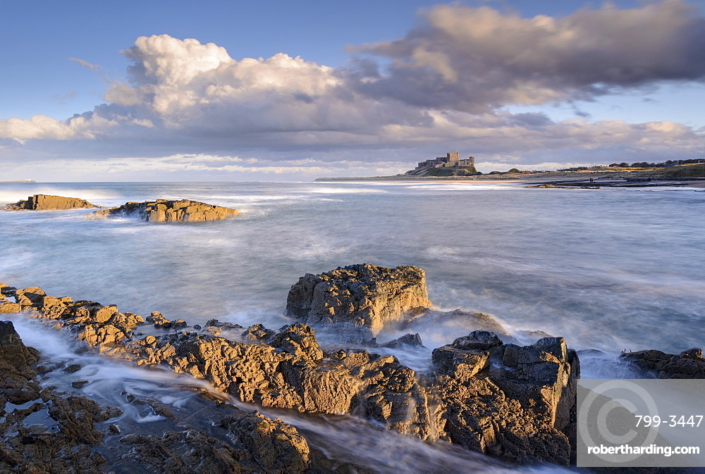 Looking across rocky ledges to Bamburgh Castle, Northumberland, England, United Kingdom, Europe