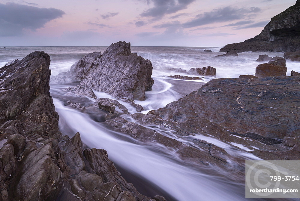 Waves surge around the jagged rocks on Wildersmouth Beach, Ilfracombe, Devon, England. Winter (January) 2019.