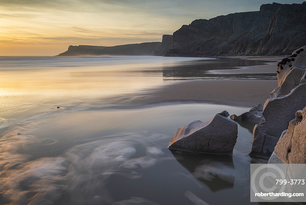 Sunset over a deserted Mewslade Bay in Gower, South Wales, UK. Winter (February) 2019.