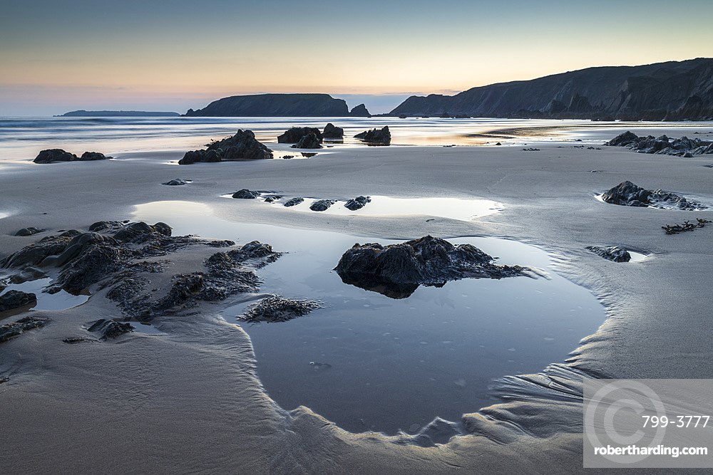 Tidal pools on Marloes Sands beach at twilight, Pembrokeshire Coast National Park, Wales, UK. Spring (March) 2019.