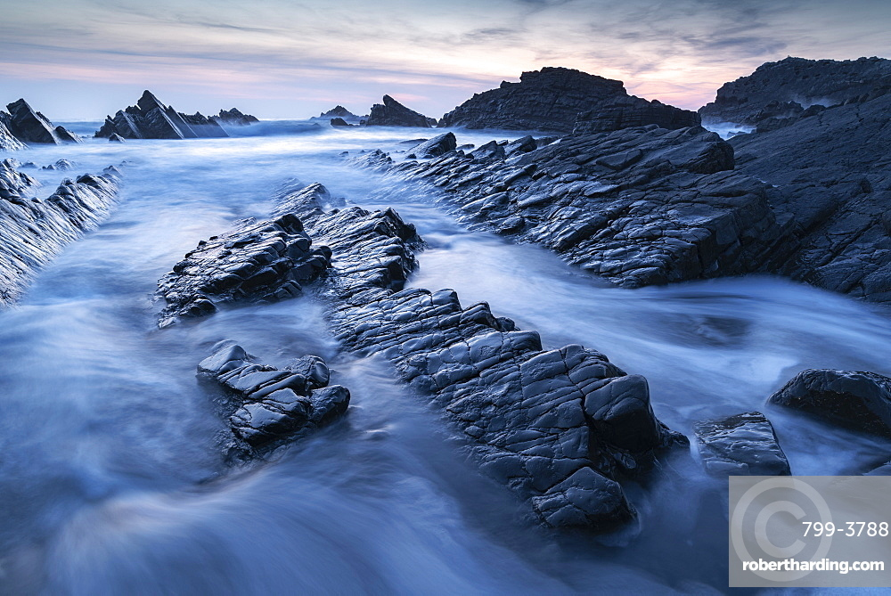 Waves and wet rock ledges at Hartland Quay in North Devon at sunset, Devon, England. Spring (April) 2019.