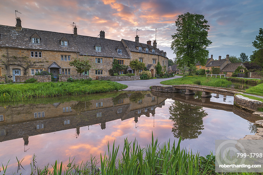 Colourful sunrise above the pretty village of Lower Slaughter in the Cotswolds, Gloucestershire, England. Spring (May) 2019.