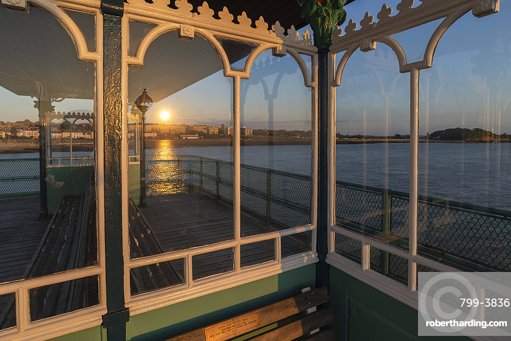 Sunset reflected in the glass shelters on Clevedon Pier, Cleveon, Somerset, England. Summer (July) 2019.