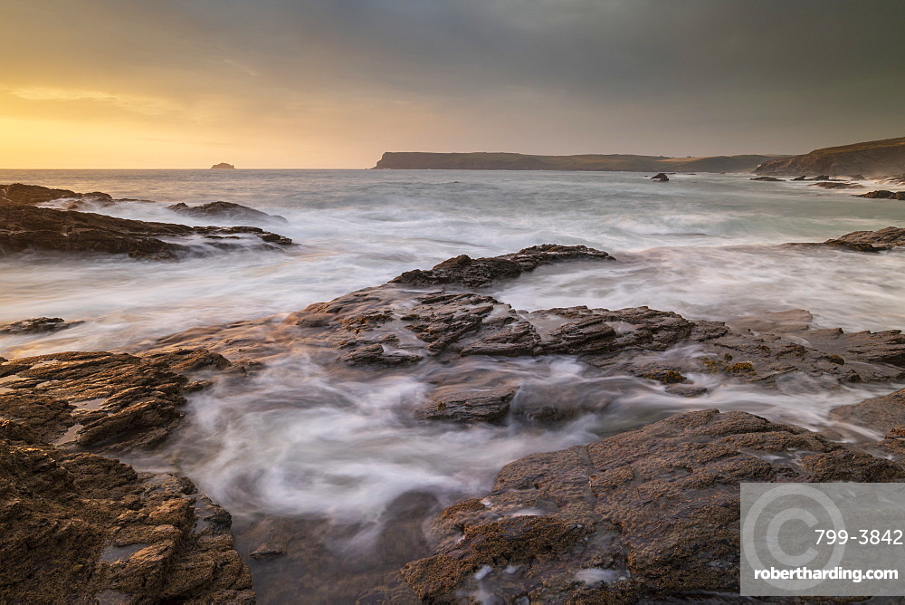 Waves swirl over rocky ledges at sunset on the North Cornwall coast, England. Summer (July) 2019.