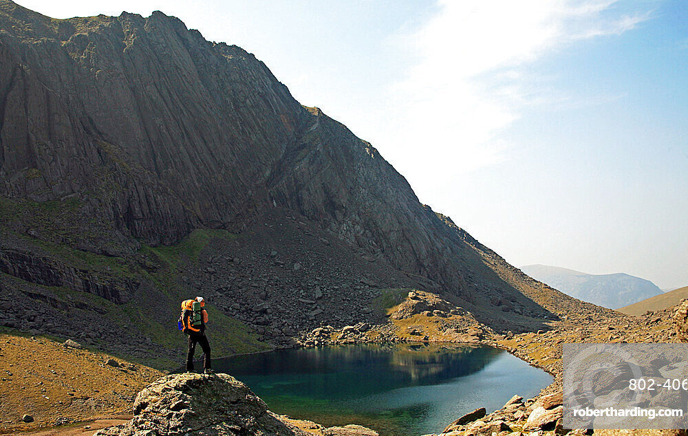 A hiker takes a break above Llyn Du'r Arddu, Snowdonia National Park, North Wales, United Kingdom, Europe