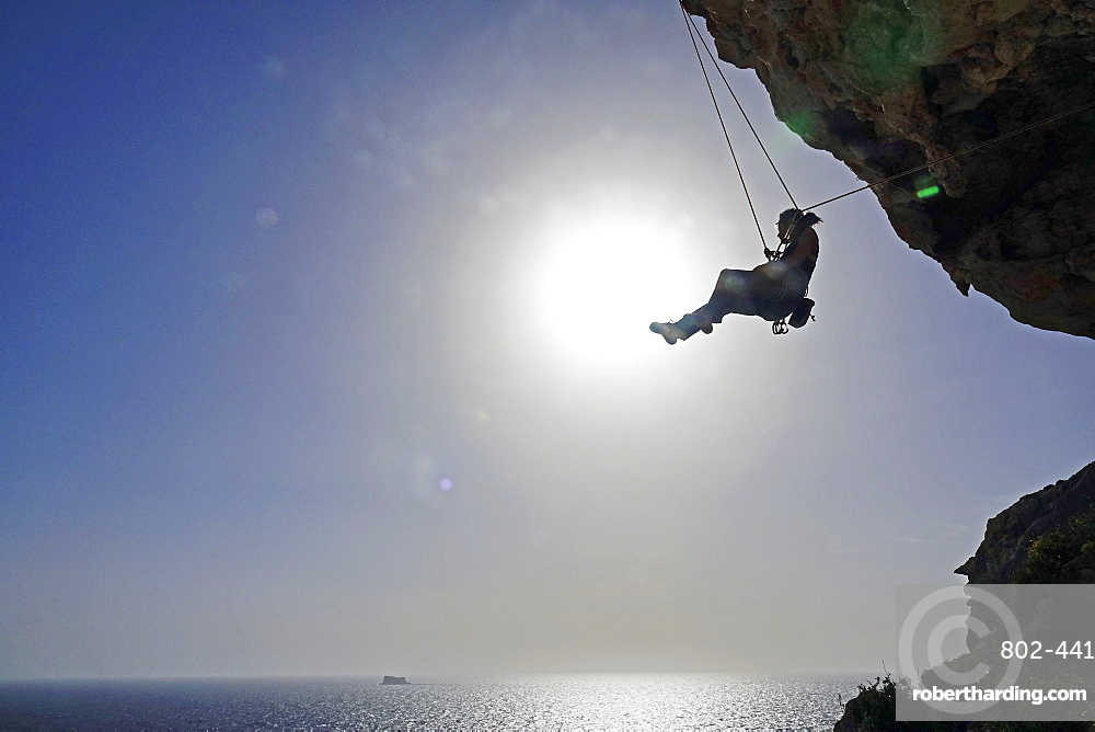 Rock climber lowering off after ascending a steep climb on the cliffs of Malta, Mediterranean, Europe