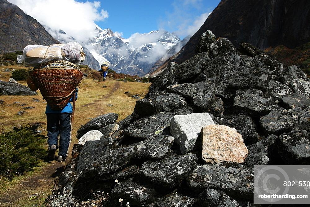 Porters pass a mani-wall, high Khumbu, Himalayas, Nepal, Asia