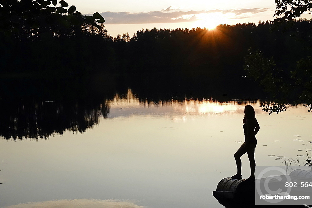 Woman looking out across a lake in rural Finland