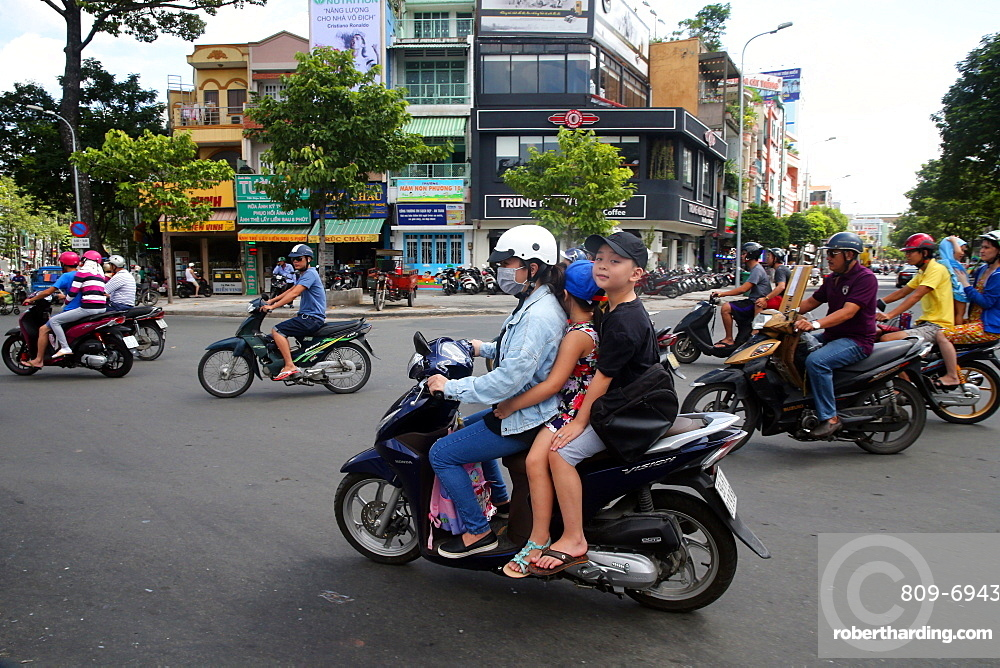 Mother and children on motor scooter on Saigon Street, Ho Chi Minh City, Vietnam, Indochina, Southeast Asia, Asia
