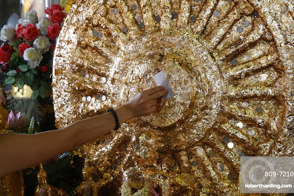 Faithful offering gold leaves in Wat Mahathat, Phetchaburi, Thailand, Southeast Asia, Asia
