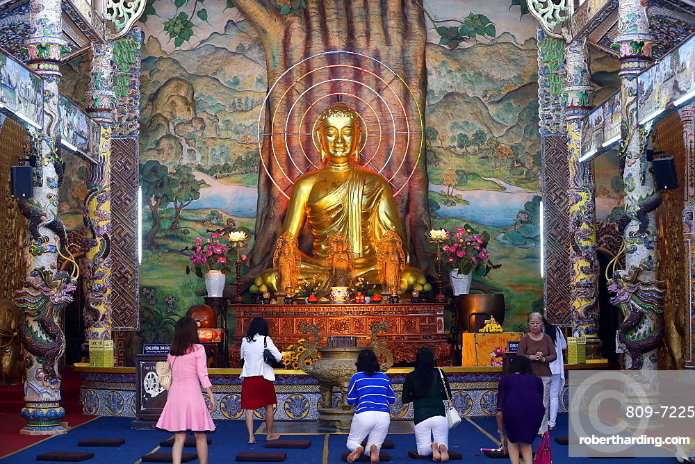 Sitting golden Buddha figure in main hall and worshippers praying to the Buddha, Linh Phuoc Pagoda, Dalat, Vietnam, Indochina, Southeast Asia, Asia