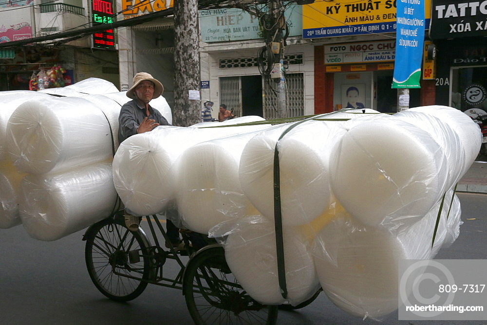 Man pedals a trishaw, loaded with rolls on a road, Ho Chi Minh City, Vietnam, Indochina, Southeast Asia, Asia