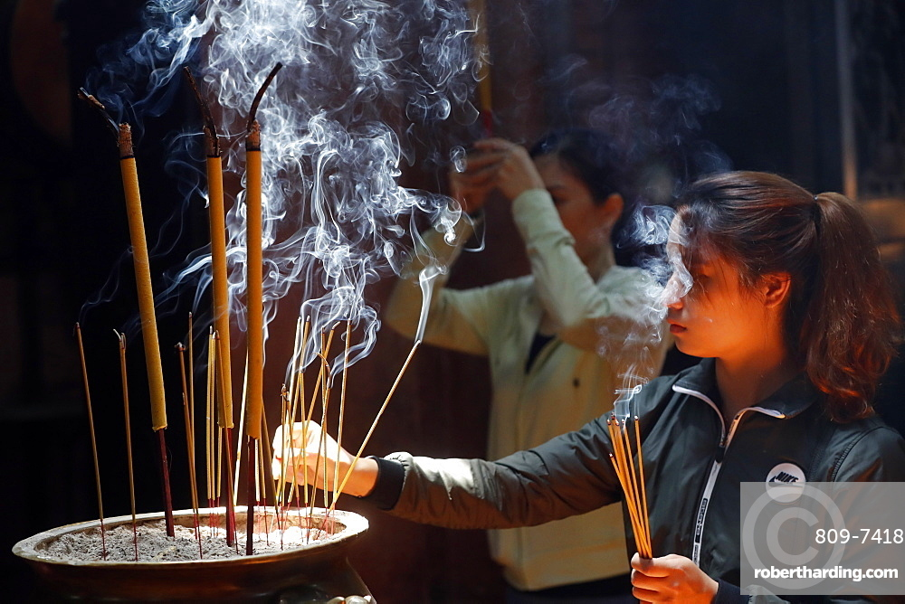 Taoist temple, Emperor Jade pagoda (Chua Phuoc Hai), Buddhist worshipper burning incense sticks, Ho Chi Minh city, Vietnam, Indochina, Southeast Asia, Asia