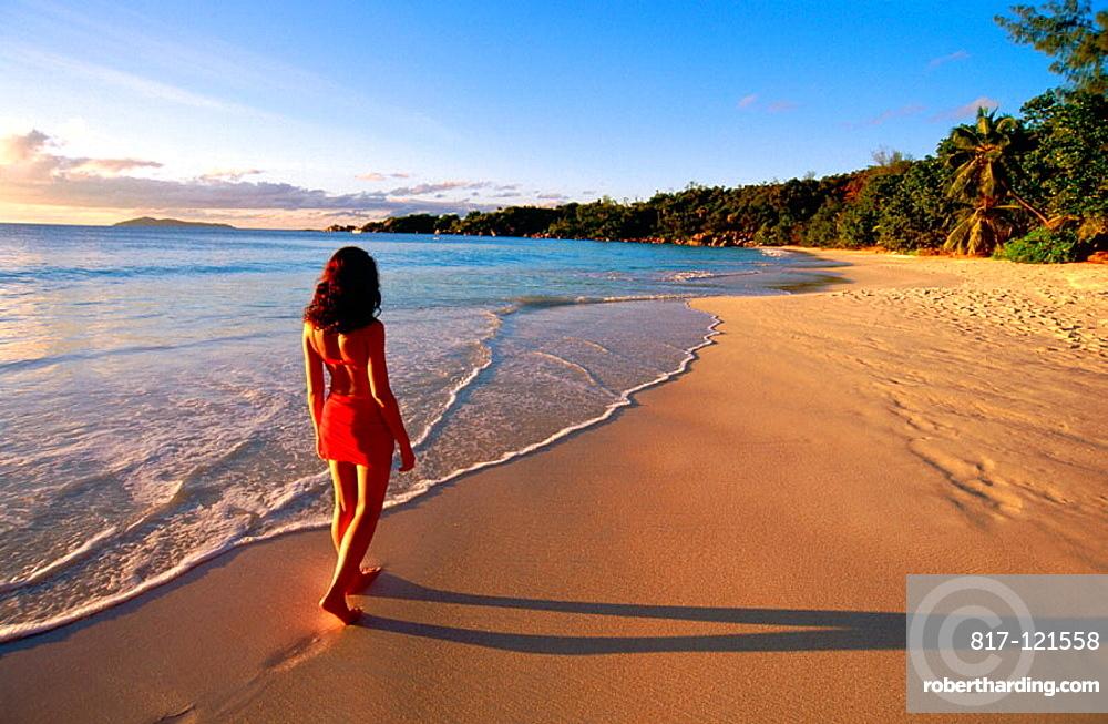 Woman walking on desert beach at sunset, Praslin Island, Seychelles