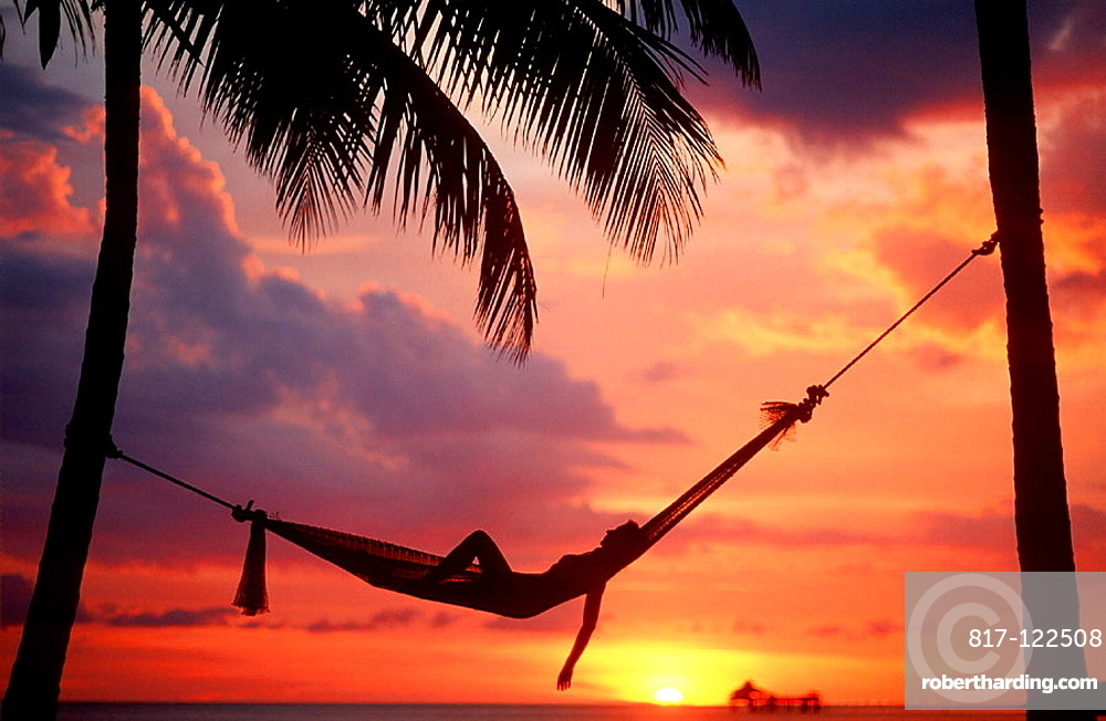 Woman asleep in hammock against palm trees and tropical sunset sky