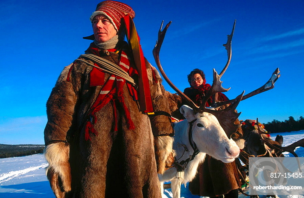 Lapps with traditional costumes and reindeer, Inari lake, Lapland, Finland.