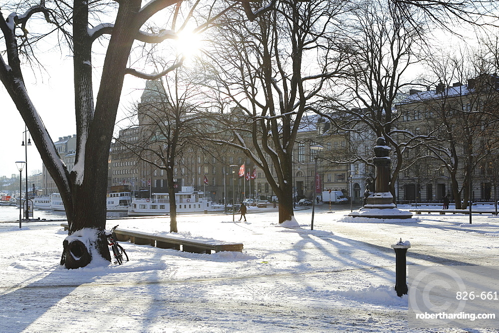 Sunshine in the snow-covered Berzelii Park, by the waterfront at Nybroviken, in Stockholm, Sweden, Scandinavia, Europe