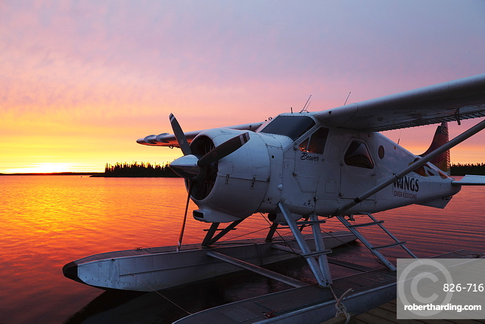 A float plane at the end of a jetty, at sunrise, in Egenolf Lake in northern Manitoba, Canada