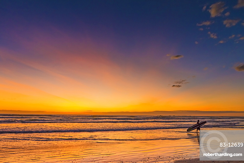 Sunset & surfer at Playa Guiones beach, Nosara, Nicoya Peninsula, Guanacaste Province, Costa Rica, Central America