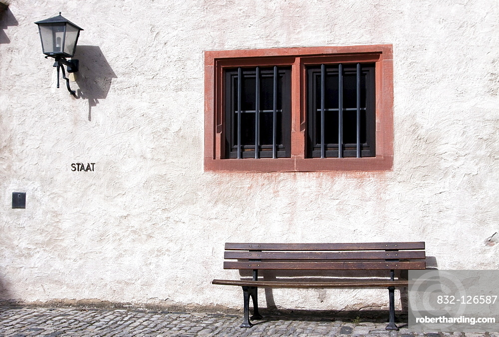 Old wooden bench below a window, Wuerzburg, Bavaria, Germany, Europe