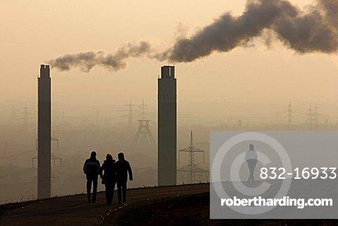 People walking across Hoheward waste dump, in front of chimneys of the AGR incinerating plant, Herten, North Rhine-Westphalia, Germany, Europe