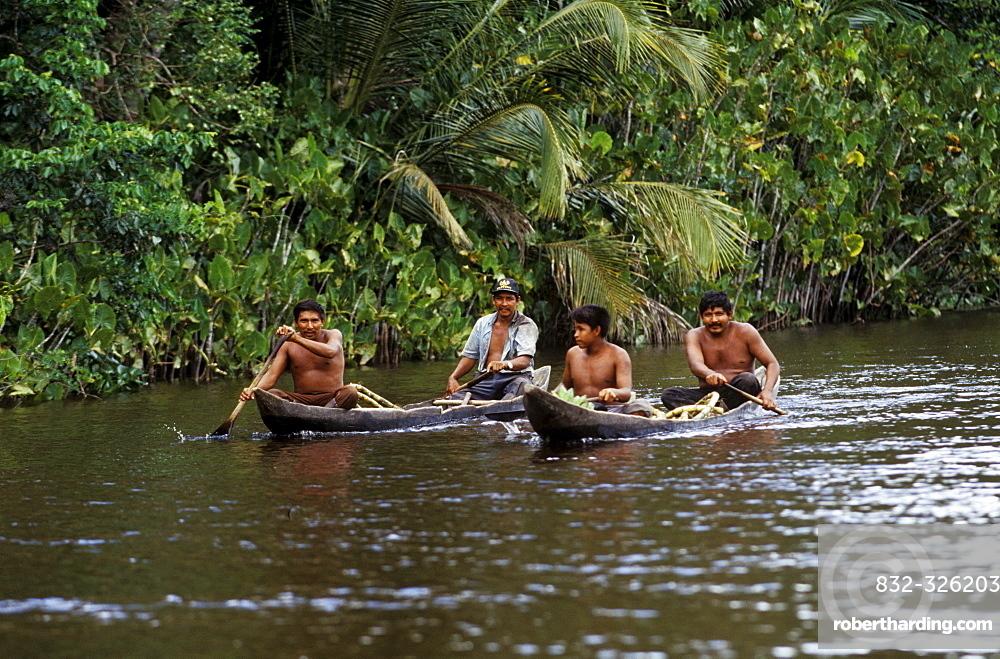 Warao Indians in a dugout canoe, Orinoco River Delta, Venezuela, South America