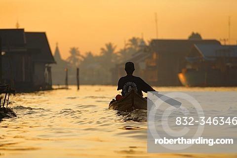 Man in boat on distributary of Sungai Barito near Banjarmasin, South-Kalimantan, Borneo, Indonesia