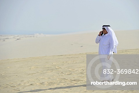Qatari on a cell phone, in traditional clothing with gutra, Emirate of Qatar, Persian Gulf, Middle East, Asia