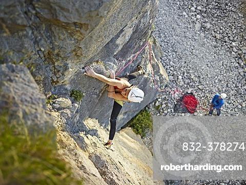 Woman lead climbing a ledge, Martinswand climbing area, Zirl, Tyrol, Austria, Europe