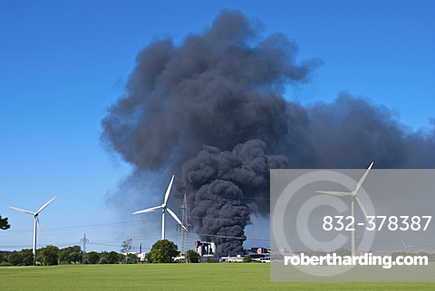 Major fire at waste recycling plant in the industrial area behind wind turbines, Melbeck, Lower Saxony, Germany, Europe