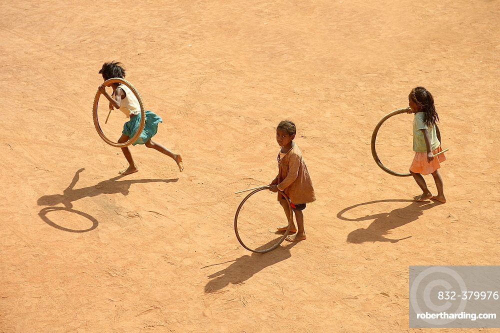 Children playing with tires on village street, Bevato, Tsiroanomandidy district, Bongolava region, Madagascar, Africa