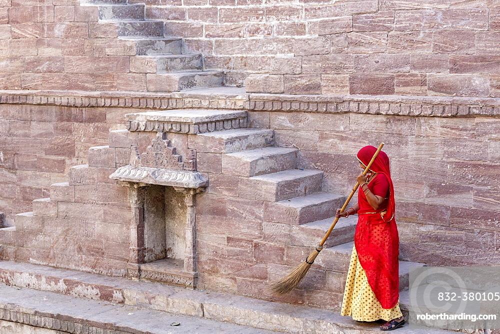 Woman in Sari cleaning the steps at Toorji Ka Jhalara, The Step Well, Jodhpur, Rajasthan, India, Asia