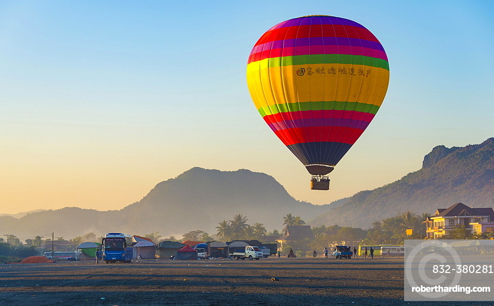 Colorful hot air balloon in the air before landing, back Karst Mountains, Vang Vieng, Vientiane Province, Laos, Asia