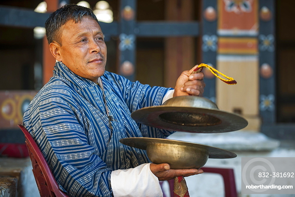 A man with cymbals at a temple festival, Mongar District, Himalayas, Kingdom of Bhutan