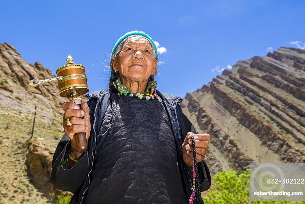An old Ladakhi woman is turning a prayer wheel, Hemis Gompa, Hemis, Jammu and Kashmir, India, Asia