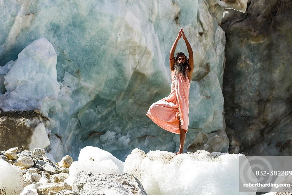 A Sadhu, holy man, is standing in tree pose, vrikshasana, on a block of ice at Gaumukh, the main source of the holy river Ganges, Gangotri, Uttarakhand, India, Asia
