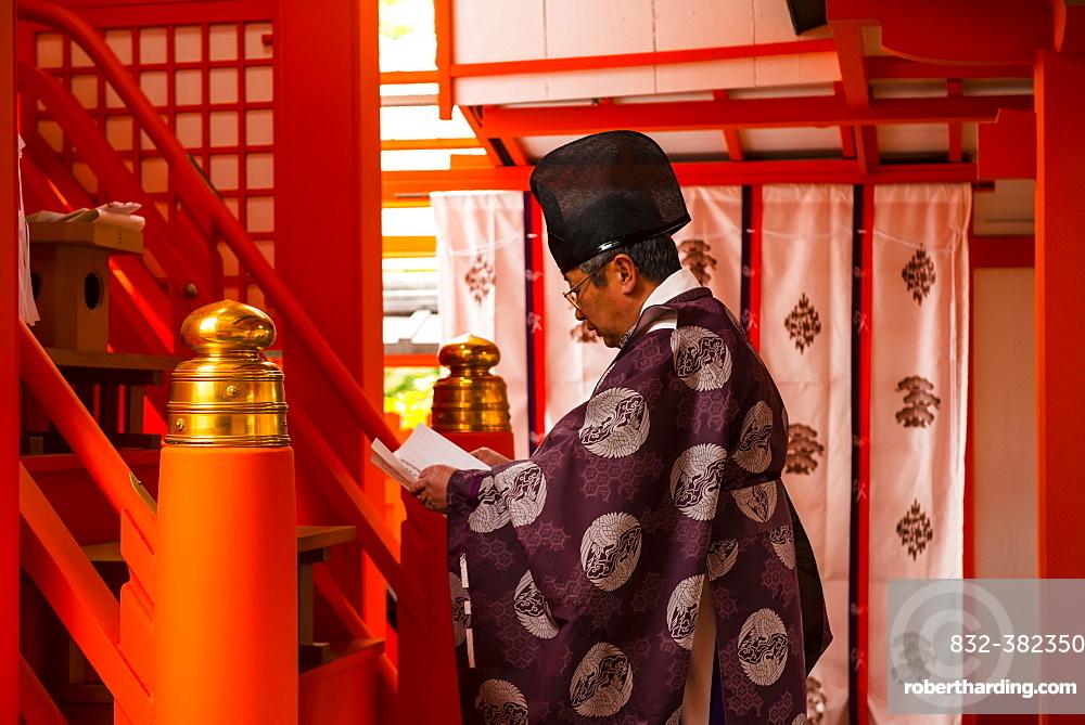 Man praying, Fushimi Inari-taisha shrine, Kyoto, Japan, Asia
