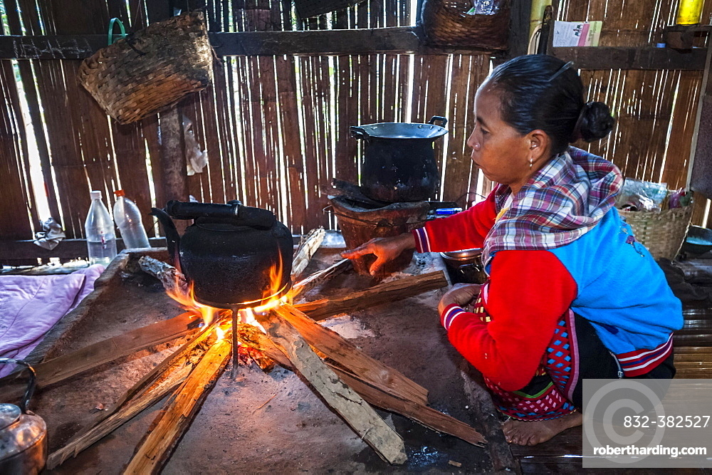 Woman from the Lahu people, hill tribe, ethnic minority, cooking on an open fire in a kitchen made of bamboo, Mae Hong Son Province, Northern Thailand, Thailand, Asia