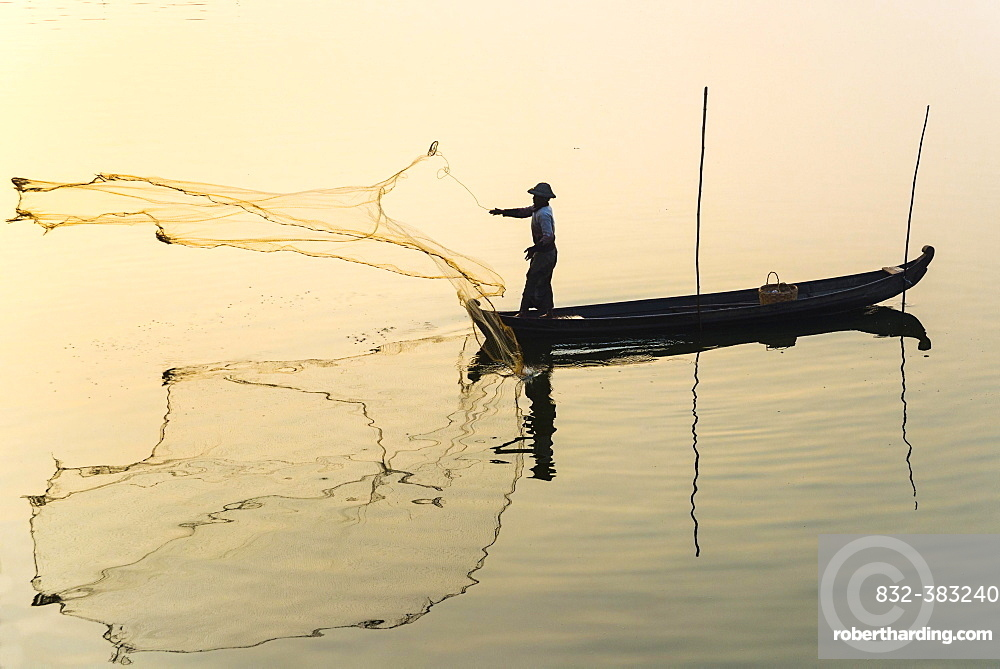 Fisherman in a boat tossing out a net, morning light, Thaungthaman Lake, Amarapura, Mandalay Division, Myanmar, Asia