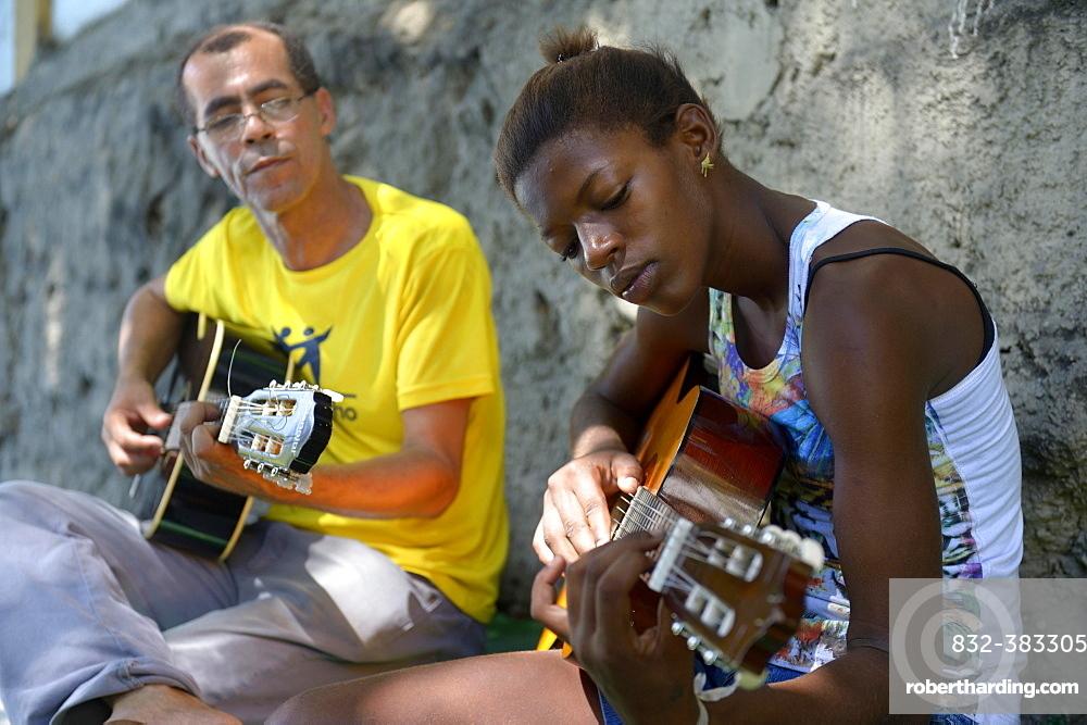 Street child, girl, 15, having guitar lessons with a social worker and musician, Sao Martinho social project, Lapa district, Rio de Janeiro, Rio de Janeiro State, Brazil, South America