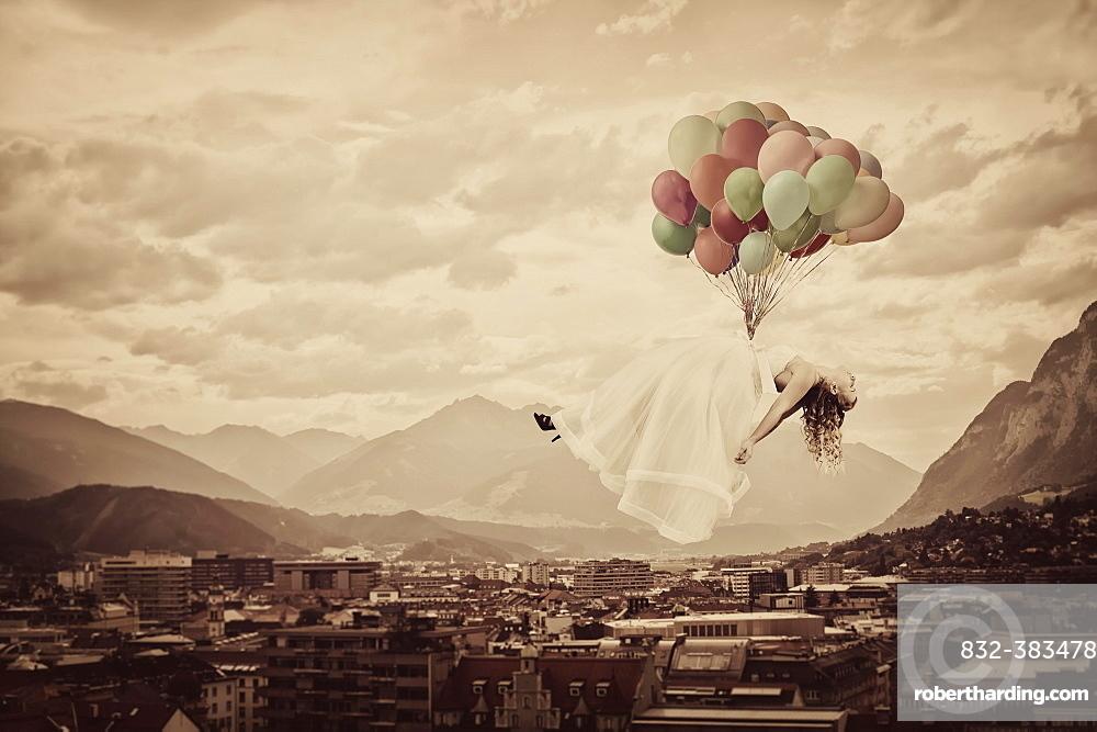 Bride floating on balloons over Innsbruck, Tyrol, Austria, Europe