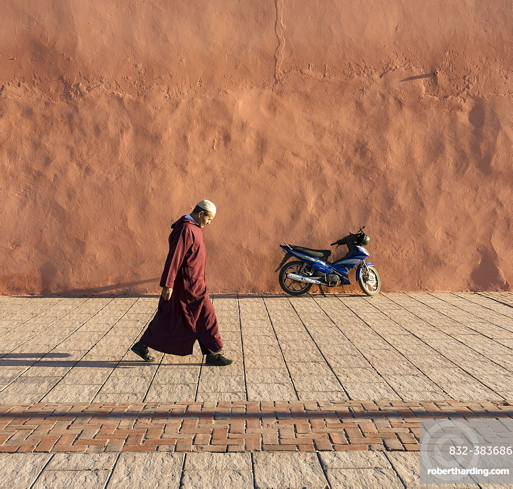 Man walks along red-orange city walls of Marrakech, Morocco, Africa