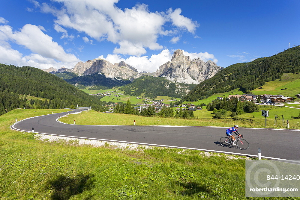 View toward Corvara and road cyclist, Alta Badia, Corvara, Dolomites, South Tyrol, Italy, Europe