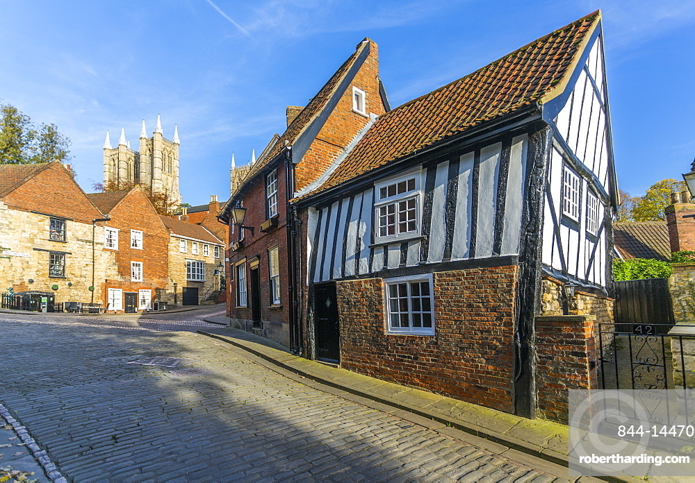 Lincoln Cathedral and timbered architecture viewed from the cobbled Steep Hill, Lincoln, Lincolnshire, England, United Kingdom, Europe